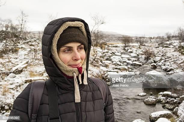 Portrait of happy woman in snowy field