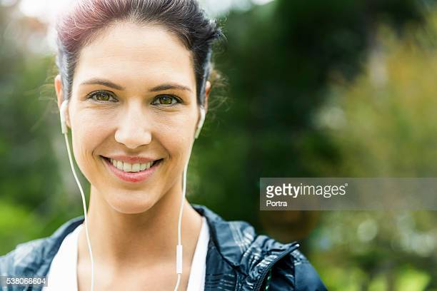 Portrait of happy woman listening to music outdoors