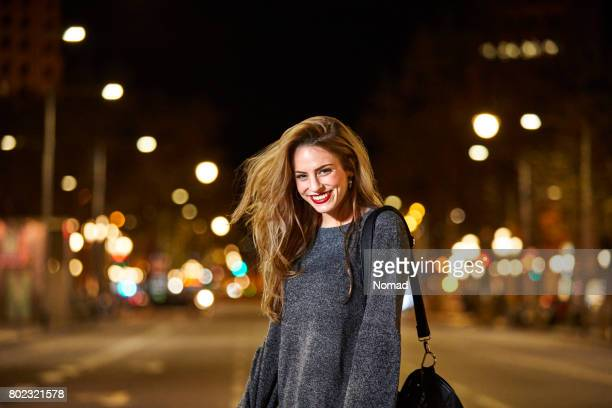 Portrait of happy woman on road in city at night