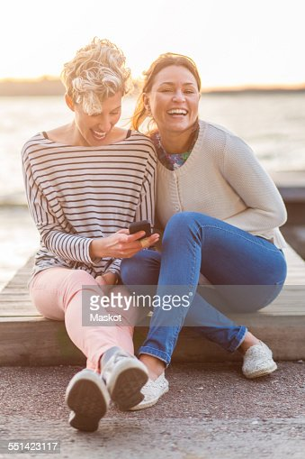 Portrait of happy woman sitting with female friend using mobile phone on pier