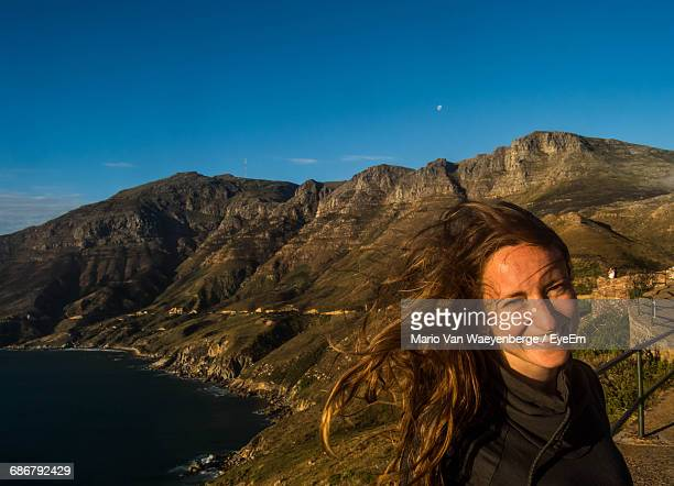 Portrait Of Happy Woman Standing Against Mountains And Blue Sky At Chapmans Peak
