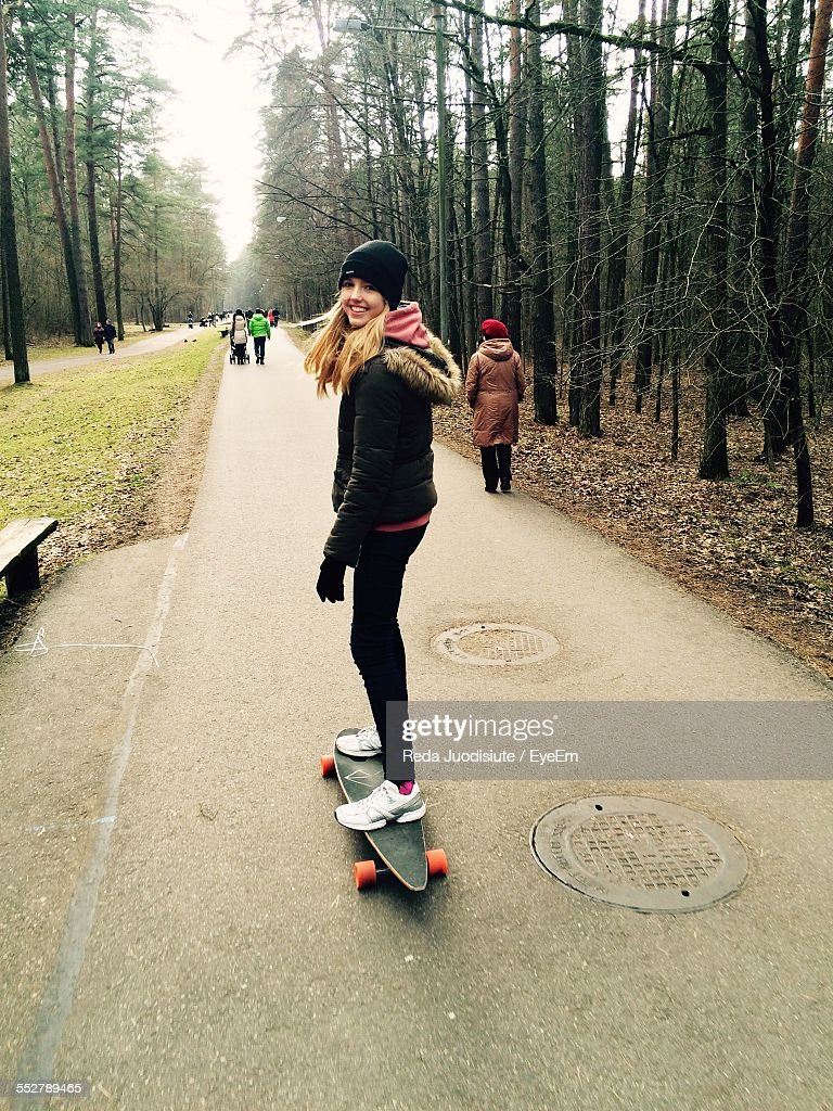 Portrait Of Happy Woman Standing On Skateboard Amidst Trees