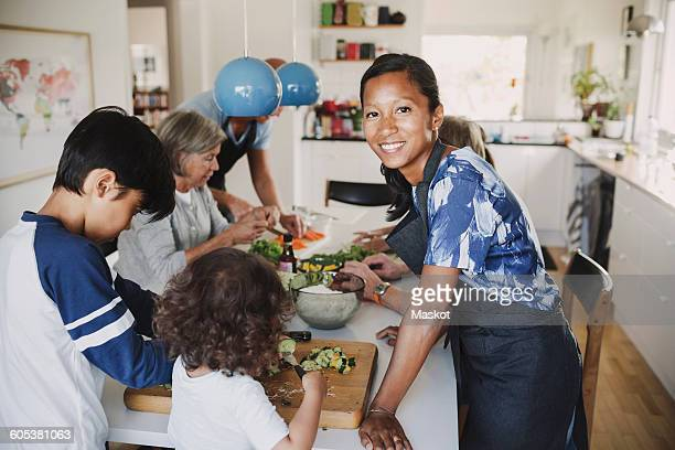 Portrait of happy woman standing with family preparing food at table in kitchen