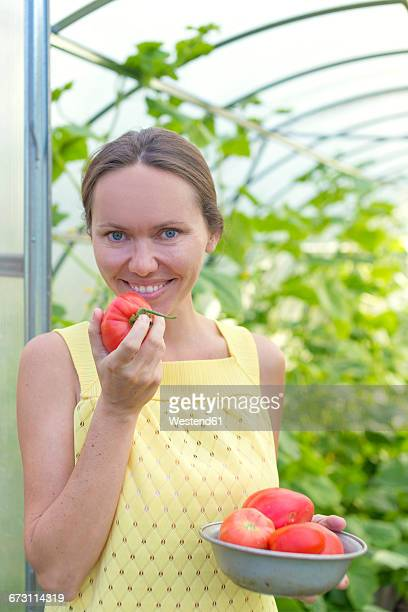 Portrait of happy woman with bowl of harvested tomatoes in front of greenhouse