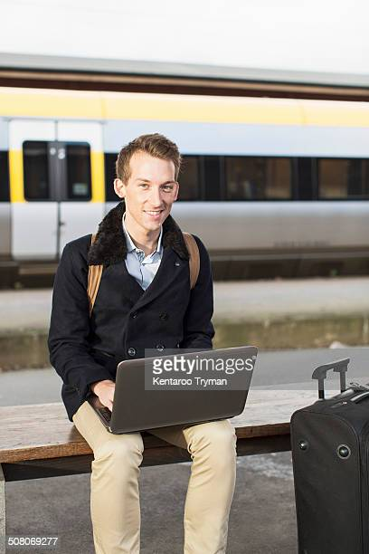 Portrait of happy young businessman using laptop on railroad station