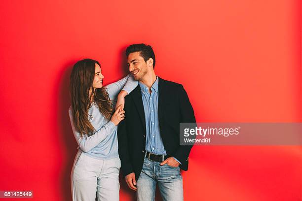 Portrait of happy young couple in front of red background