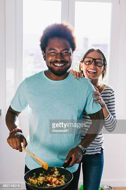 Portrait of happy young couple in their kitchen