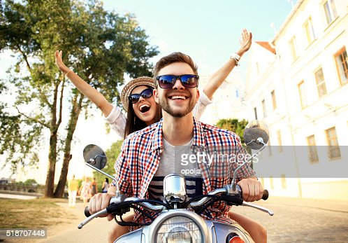 Portrait of happy young couple on scooter enjoying road trip : Stock Photo