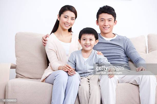 Portrait of happy young family sitting in sofa