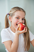 Portrait of happy young girl eating an apple over gray background