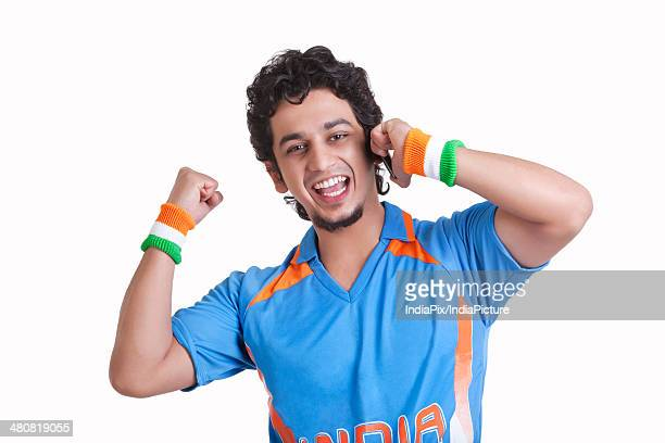 Portrait of happy young man in jersey cheering while answering phone call over white background