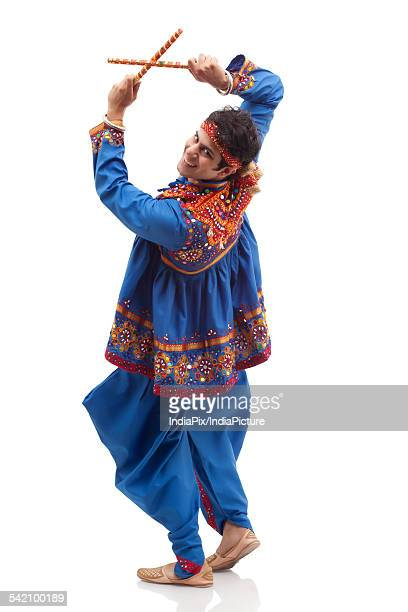 Portrait of happy young man in traditional clothes performing Dandiya Rass isolated over white background