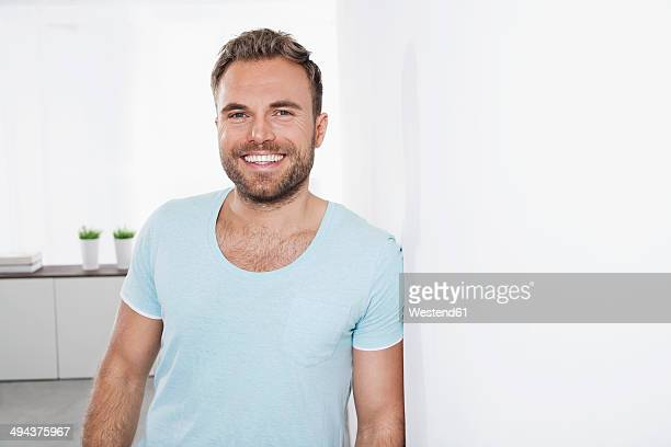 Portrait of happy young man leaning against wall