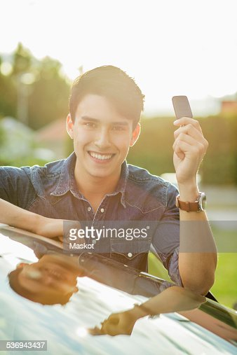 Portrait of happy young man showing key while leaning on car
