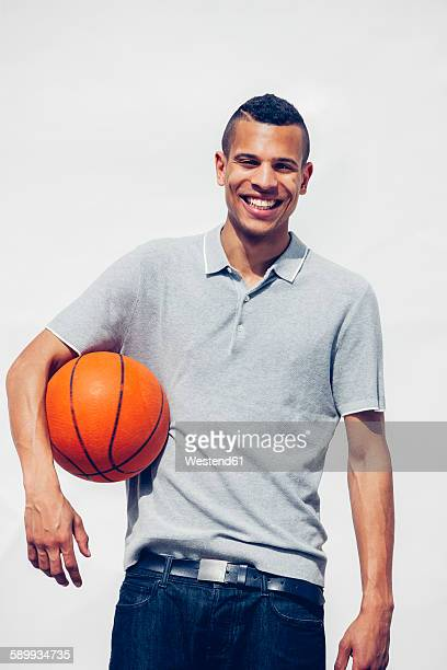 Portrait of happy young man with basketball in front of white background