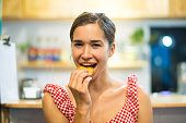 Portrait of happy young woman eating cookie in kitchen. Latin American woman biting pastry with pleasure. Food concept