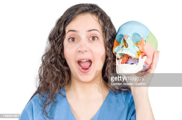 Portrait Of Happy Young Woman Holding Colorful Human Skull Against White Background