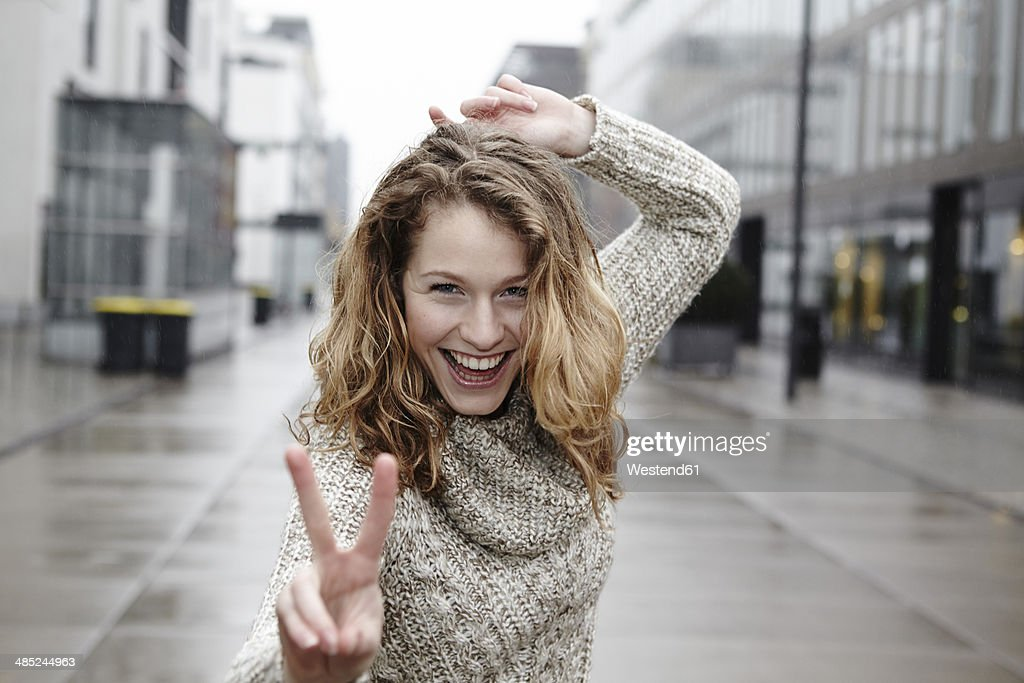 Portrait of happy young woman showing victory sign