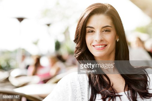 Portrait of happy young woman sitting at a pavement cafe