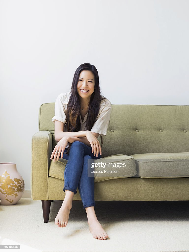 portrait of happy young woman sitting on sofa stock photo. Black Bedroom Furniture Sets. Home Design Ideas