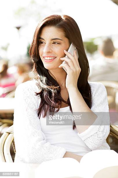 Portrait of happy young woman telephoning with smartphone at a pavement cafe