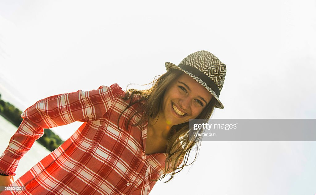 Portrait of happy young woman wearing hat outdoors
