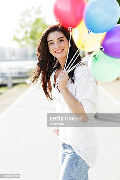 Portrait of happy young woman with a bunch of balloons