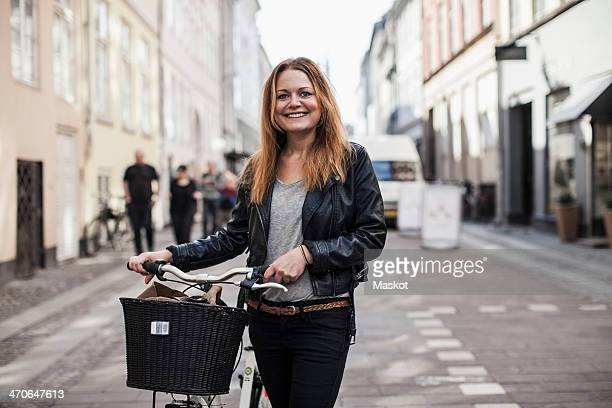 Portrait of happy young woman with bicycle standing on city street