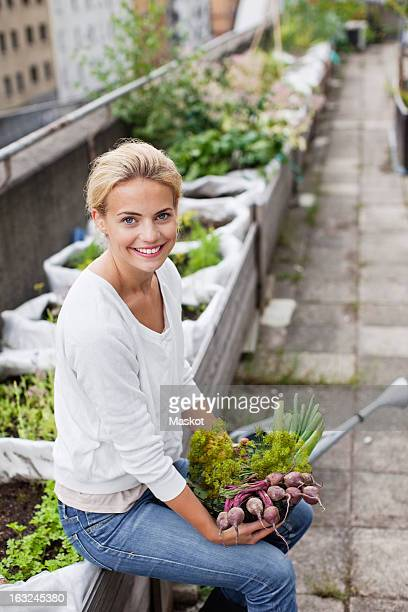 Portrait of happy young woman with freshly harvested vegetables at urban garden