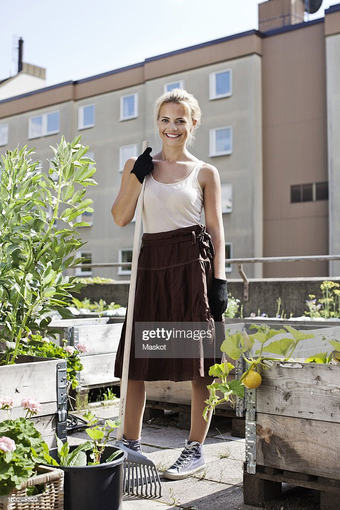 Portrait of happy young woman with gardening fork standing at urban garden