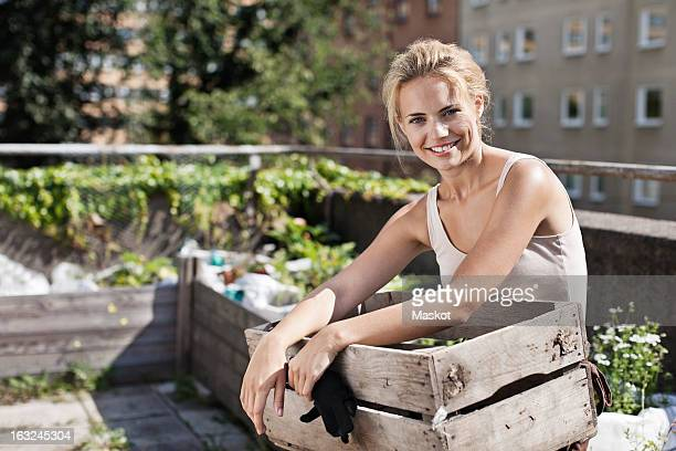 Portrait of happy young woman with wooden crate sitting at urban garden
