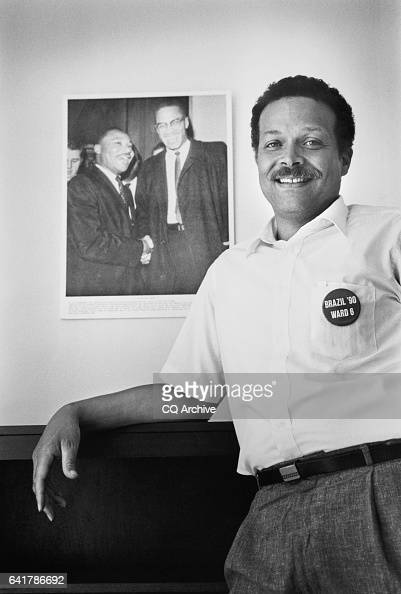 Portrait of Harold Brazil DDC Council Member standing with his poster of Martin Luther King Jr and Malcolm X June 28 1990