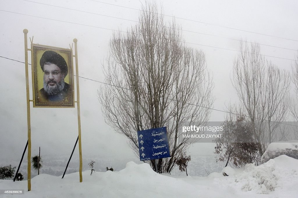 A portrait of Hassan Nasrallah, the leader of Lebanese Hezbollah movement, stands during a snowstorm in the Rihan Mountains region in southern Lebanon on February 20, 2015. Blizzards dumped a blanket of snow over Israel, Jordan and Lebanon, with many residents urged to stay in their homes because of blocked or icy road. AFP PHOTO / MAHMOUD ZAYYAT