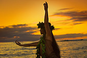 A beautiful Hawaiian Hula dancer dancing on the beach of the tropical Hawaiian islands. She is wearing a traditional Hula dance dress with a lei and a head dress. Photographed at sunset in horizontal