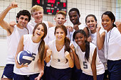 Portrait Of High School Volleyball Team Members With Coach Holding Ball Smiling To Camera