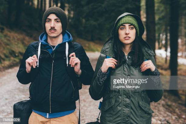 Portrait of hiking couple wearing knit hats in forest, Monte San Primo, Italy