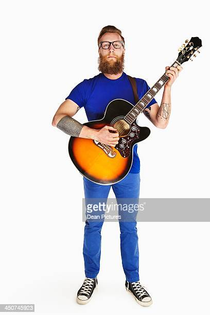 Portrait of hip young man holding guitar