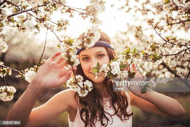 Portrait of hippie girl trought cherry blossom tree