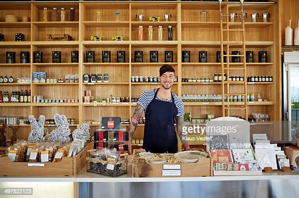 Portrait of hipster clerk in deli shop