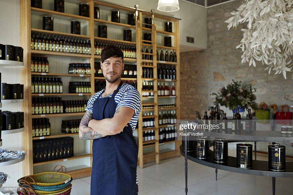 Portrait of hipster clerk in olive oil shop
