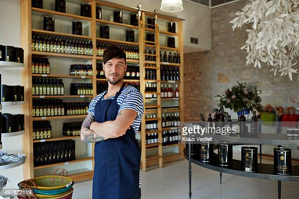 Portrait of hipster clerk in olive oil shop