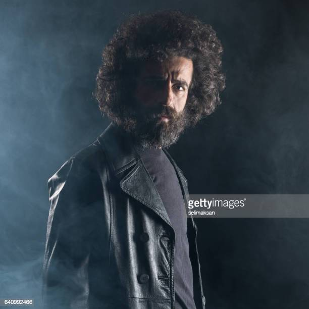 Portrait Of Hipster With Beard And Long Hair Wearing Leather Jacket In Dark