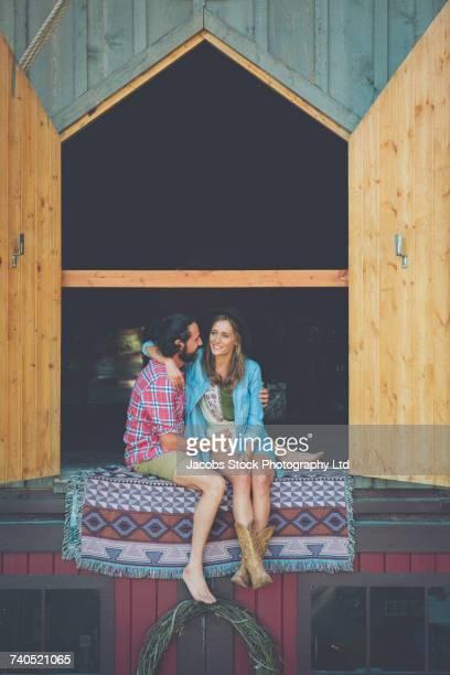 Portrait of Hispanic couple sitting near open barn doors