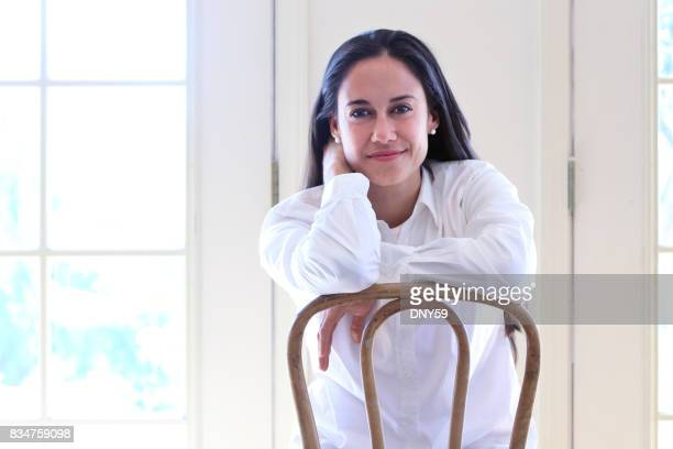 Portrait Of Hispanic Female Millennial Sitting In Chair At Home