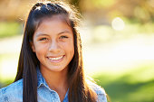 Portrait Of Hispanic Girl In Countryside Smiling To Camera