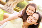 Portrait Of Hispanic Mother And Daughter In Park Smiling To Camera