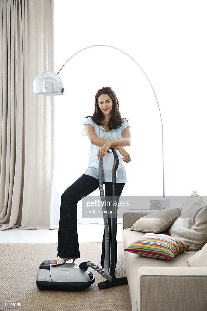 Portrait of Hispanic woman cleaning with vacuum : Stock Photo