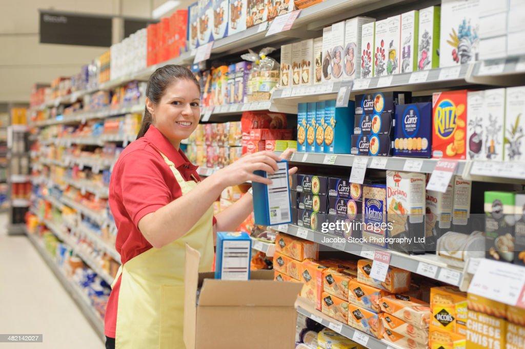 Portrait of Hispanic worker stocking shelves in supermarket
