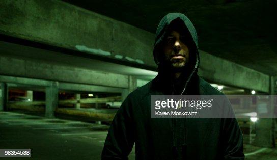 portrait of hooded man in empty parking garage