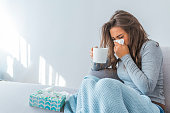 Cold And Flu. Portrait Of Ill Woman Caught Cold, Feeling Sick And Sneezing In Paper Wipe. Closeup Of Beautiful Unhealthy Girl Covered In Blanket Wiping Nose. Healthcare Concept. High Resolution